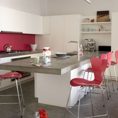 White open plan kitchen fitted units island breakfast bar unit with concrete worktop pink red bar stools by designer Arne Jacobseb Series 7 concrete floor real home L etc 02/2009 pub orig